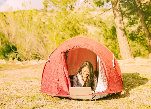 Female traveler working with laptop in camping