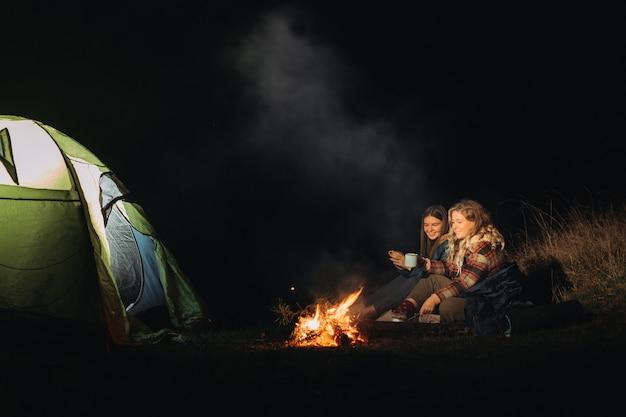 焚き火の近くに座っている女性旅行者