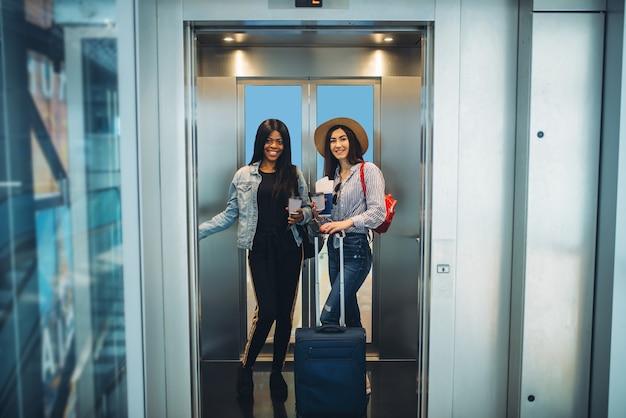空港エレベーターの荷物を持つ女性旅行者