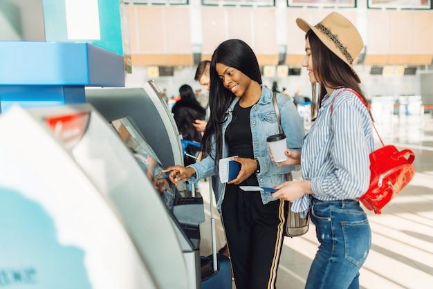 女性旅行者が空港のatmで現金を引き出す
