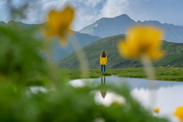 黄色いジャケットを着た女性旅行者が湖のほとりに立っている美しい水面に映る