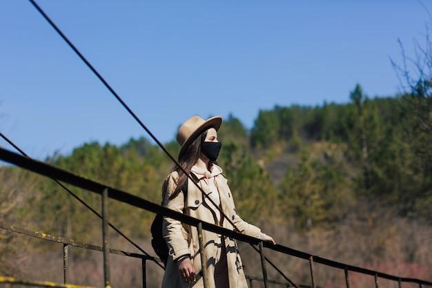 女性旅行者はウイルスから保護し、吊橋の上に立つためにフェイスマスクを着用します
