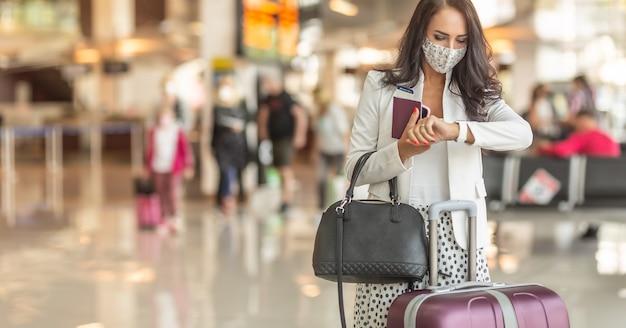핸드백, 여행 가방, 얼굴 마스크를 쓴 여권을 가진 여성 여행자는 공항 홀에서 시간을 확인합니다.