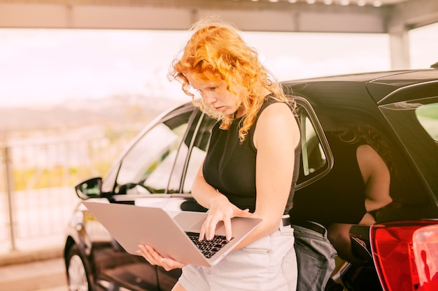 Female traveller with laptop standing beside car