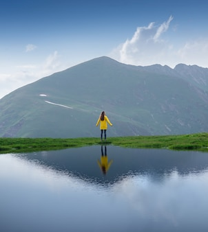 Female traveller in a yellow jacket stands on the shore of a lake beautiful reflection in the water