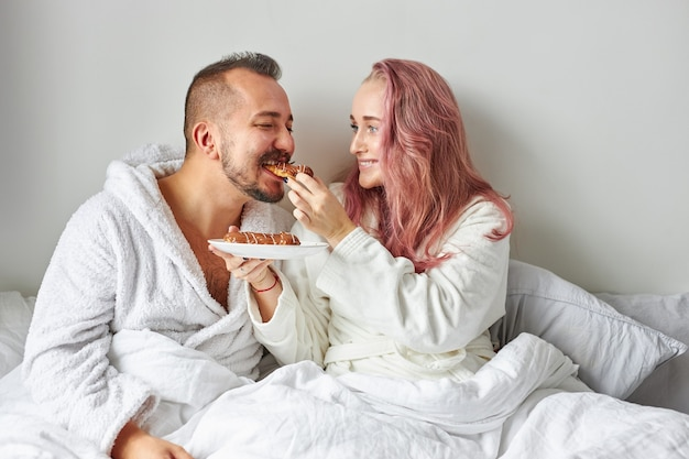 Женщина угощает мужа круассанами эклерами, кавказская пара на кровати утром
