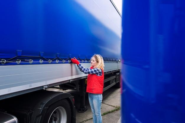 Водитель грузовика женского пола проверяет автомобиль и затягивает брезент грузовика