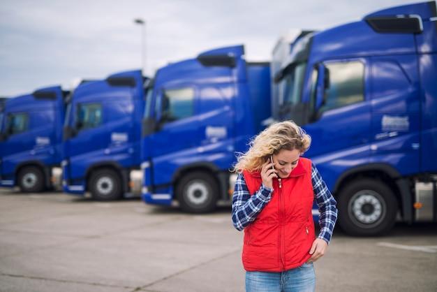 Водитель грузовика женского пола разговаривает по телефону о грузе, который должен быть доставлен