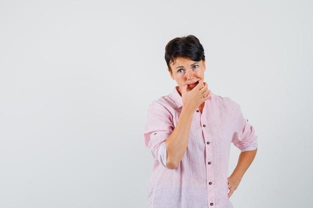 Donna che prova a fischiare in camicia rosa e che sembra pensierosa. vista frontale.