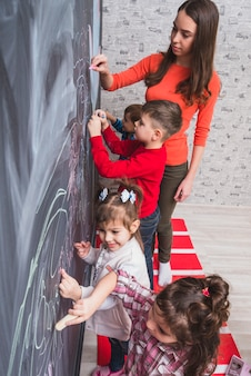 Female tutor drawing on blackboard with kids
