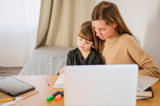 Female tutor teaching child at home with laptop