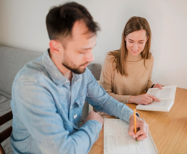 Female tutor teaching male student at home