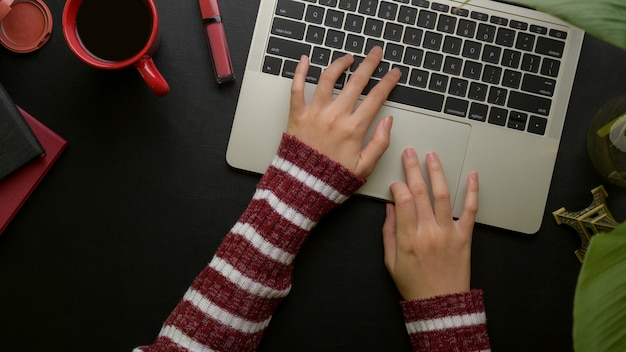 Female typing on laptop keyboard on stylish office desk with office supplies, camera and cosmetics