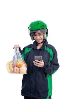 ヘルメットをかぶった女性のユーバー配達宅配便は、白い背景の上に分離されたビニール袋に食料品をもたらします
