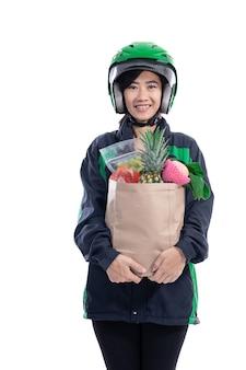 ヘルメットをかぶった女性のユーバー配達宅配便は、バッグに食料品を持ってきます