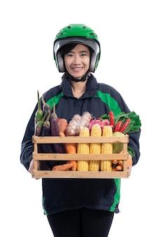 ヘルメットをかぶった女性のユーバー配達宅配便は、木枠に食料品をもたらします