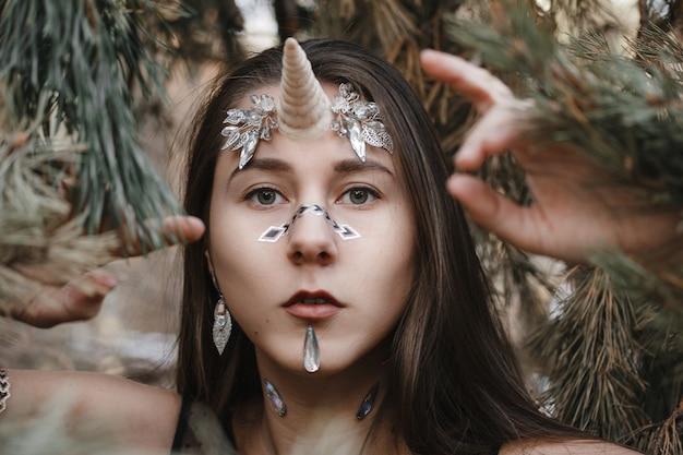 クリスタルの女性ユニコーン。森の中の雪の上を歩く妖精の女の子ユニコーン。 Premium写真