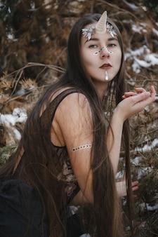 クリスタルの女性ユニコーン。森の中の雪の上を歩く妖精の女の子ユニコーン。