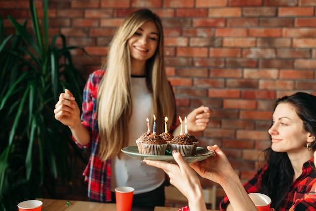 Студентка университета получает сладкий подарок от подруг. молодежь за столом в квартире, домашняя вечеринка, празднование дня рождения