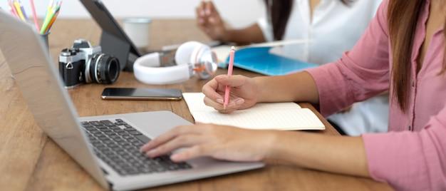 図書館のテーブルでデジタルデバイスや文房具と一緒に割り当てを行う女子大生