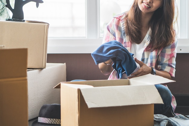 Female unpacking clothes and stuffs  from cardboard box after relocate from apartment to n