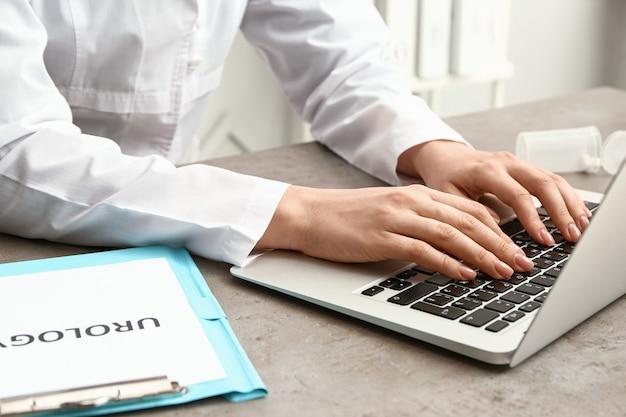 Женский уролог, работающий на ноутбуке за столом