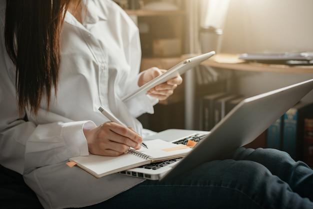 女性は朝、ホームオフィスのノートにメモを取るためにタブレットとラップトップコンピューターを使用します。