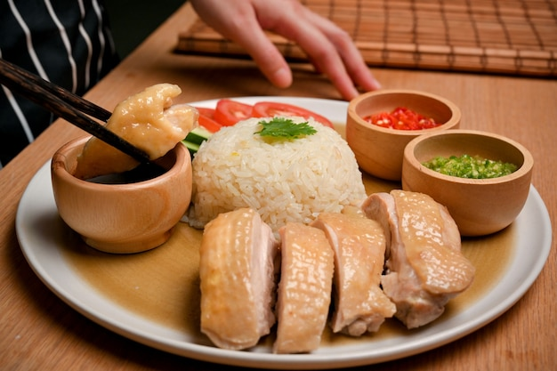 女性は箸を使って、甘い醤油に浸した鶏肉をつかみます海南鶏飯