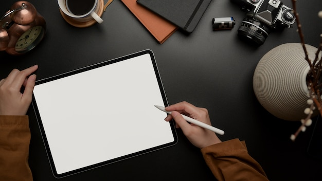 Female using blank screen tablet with stylus on office desk with camera supplies and decoration