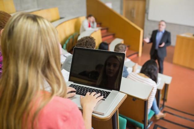 강당에서 학생 및 교사와 노트북을 사용하는 여성