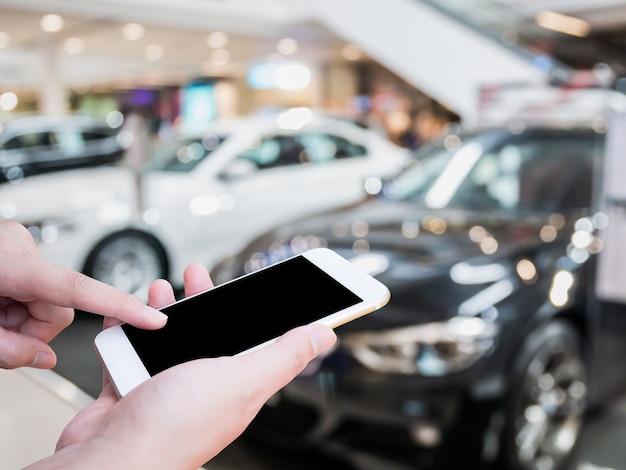 新しい車が背景にぼやけている自動車ショールームで携帯スマートフォンを使用している女性