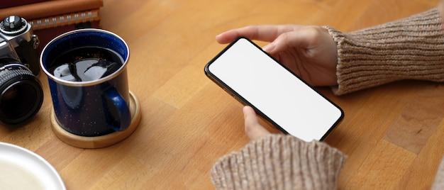 コーヒーカップ、カメラ、消耗品と木製のテーブルでスマートフォンをモックを使用して女性