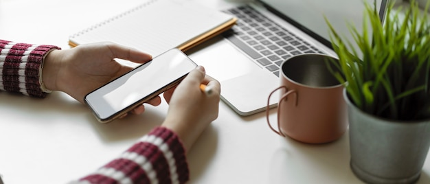 Female using mock up smartphone on white table with laptop, notebook, mug and plant pot