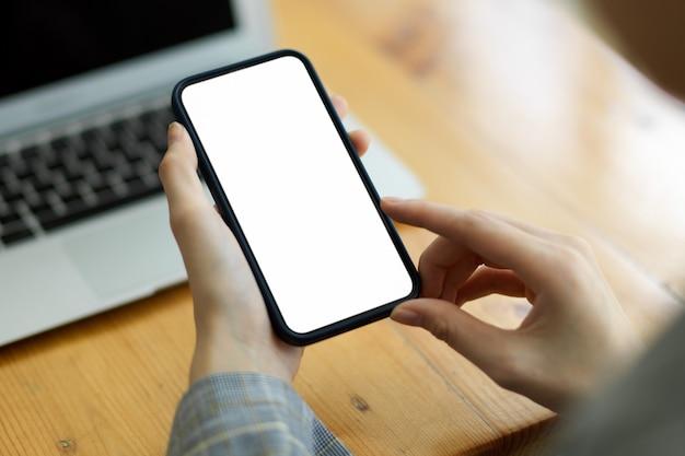 Женщина, использующая смарт-мобильный телефон для сообщений и просмотра веб-сайтов в размытом рабочем пространстве в фоновом режиме