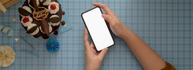 ケーキとデコレーションで青い背景にスマートフォンを使用して女性