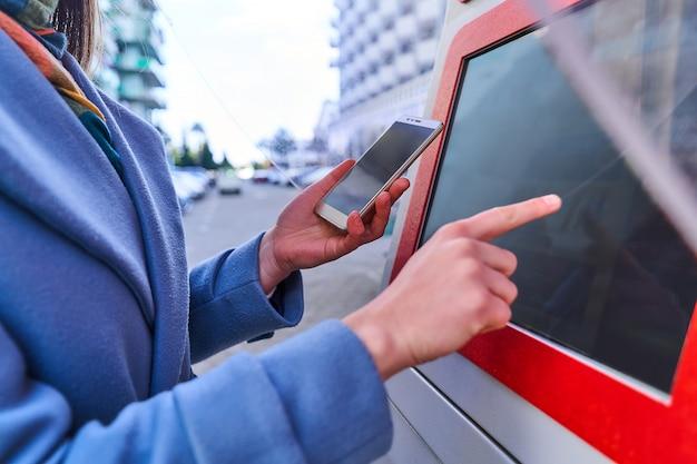 Женщина использует уличный терминал самообслуживания и смартфон для оплаты услуг