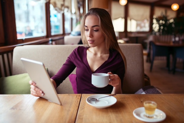 Female using wifi on tablet pc in cafe