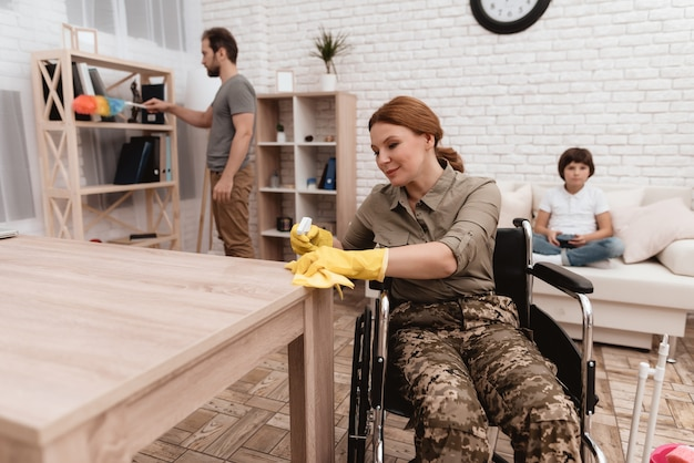 A female veteran in a wheelchair is cleaning the house.