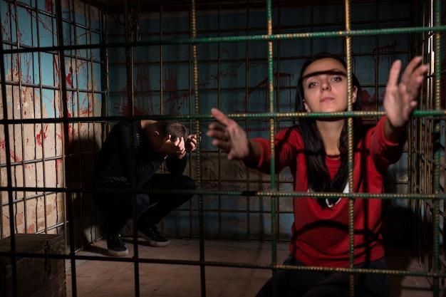 Жертва заключена в металлическую клетку с забрызганной кровью стеной, протягивающей руки через решетку, испуганный мужчина сидит в углу