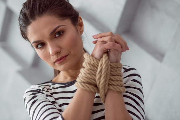 Female victim. sad moody cheerless woman holding her hands together and looking at you while being tied up