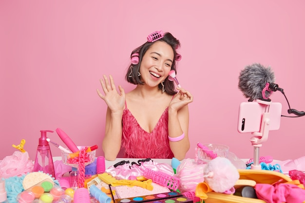 Female video blogger streaming online workshop uses cosmetic brush makes hairstyle with rollers sits in front of smartphone webcam wears fashionable pink dress