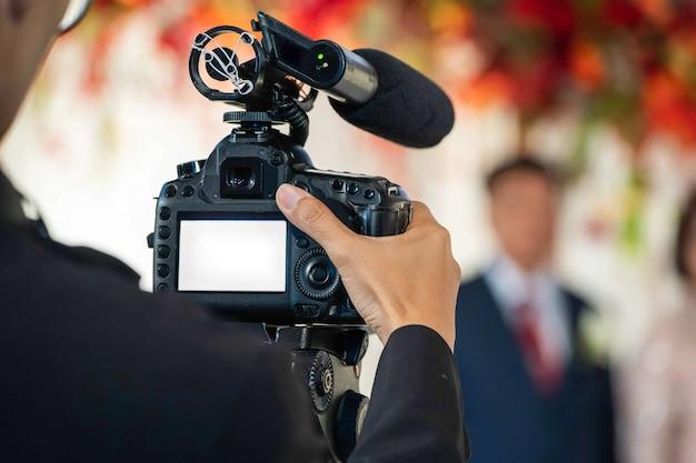 裏側の女性ビデオグラファーが結婚式のイベントでビデオを撮影して録画しています。