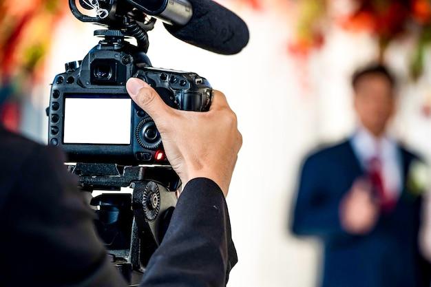 Женщина-видеооператор сзади снимает и записывает видео в свадебном мероприятии.
