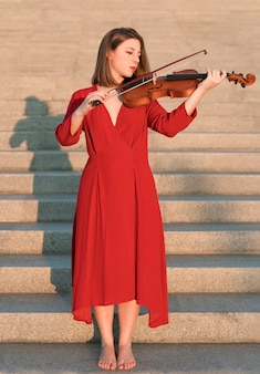 Скрипачка играет на инструменте на ступеньках