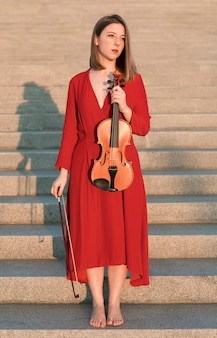 Female violinist posing on steps with violin