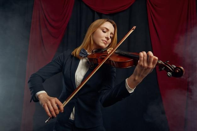 Скрипачка с смычком и скрипкой, выступление на сцене. женщина со струнным музыкальным инструментом, музыкальное искусство, музыкант играет на альте