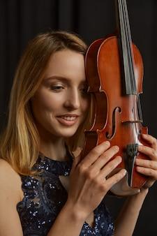 Женский скрипач с ретро скрипкой на ее лице. женщина со струнным музыкальным инструментом, музыкальное искусство, музыкант играет на альте