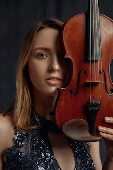 Female violonist with retro violin at her face. woman with string musical instrument, music art, musician play on viola