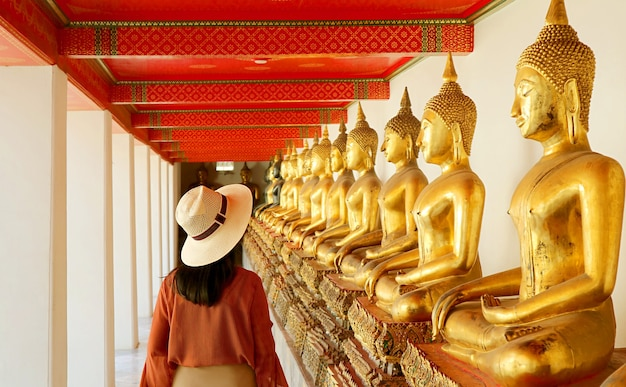 タイのワットポー寺院で座っている仏像の大規模なグループと回廊を訪れる女性
