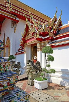 Female visitor entering the ornate inner entrance of temple of the reclining buddha or wat pho, bangkok, thailand